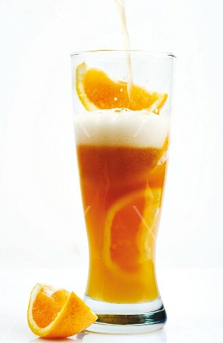 Pouring Hefeweizen Beer into a Glass Filled with Orange Wedges; Symbolic to show Citrus Flavor of Beer