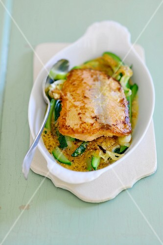 Fried salmon fillet on a bed of courgette wedges