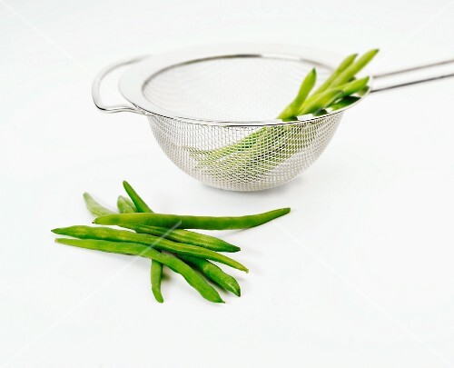 Fresh runner beans in and next to a sieve