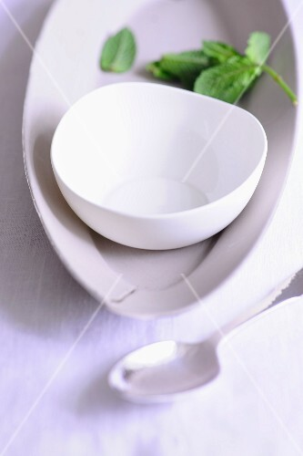 White crockery, a dessert spoon and mint leaves