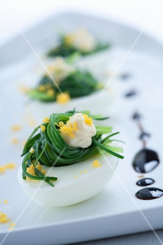 Eggs filled with buck's horn plantain and sprinkled with egg yolk; with balsamic vinegar