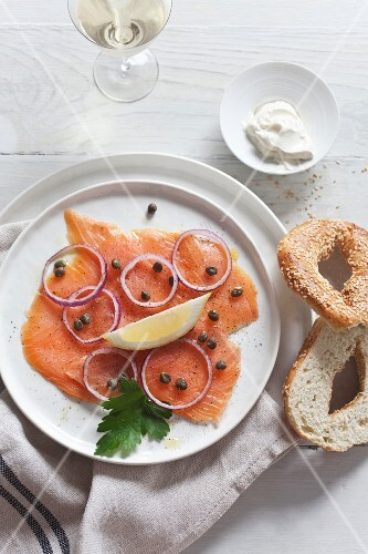 Smoked salmon with capers and onions served with a sesame seed bagel and crème fraîche