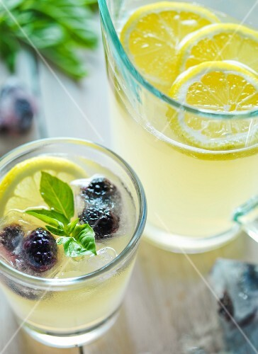 Glass of Lemonade with Blackberries and Basil; Pitcher of Lemonade