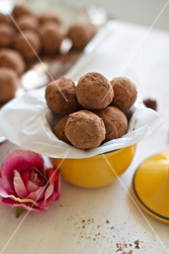 Small Yellow Bowl of Vegan Chocolate Citrus Truffles with a Pink Flower