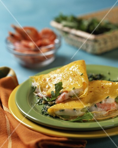 Crepes filled with béchamel and prawns on rocket