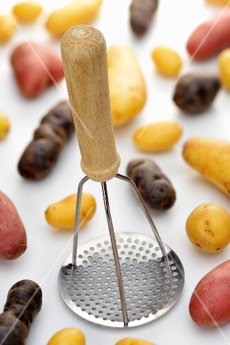 Potato masher and colourful potatoes