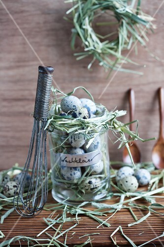 Whisk leaning on jar filled with quails' eggs and wreathed in hay