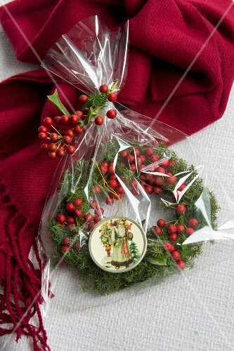 Wreath of holly berries with Father Christmas pendant wrapped as present