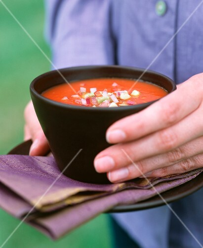 A hand holding a bowl of spicy tomato soup