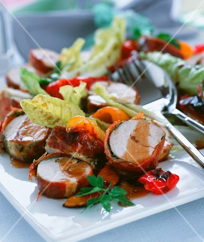 Chicken with herbs, wrapped in prosciutto and served with vegetables and salad
