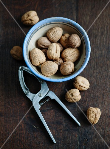 Walnuts in a bowl and a nutcracker on a wooden surface