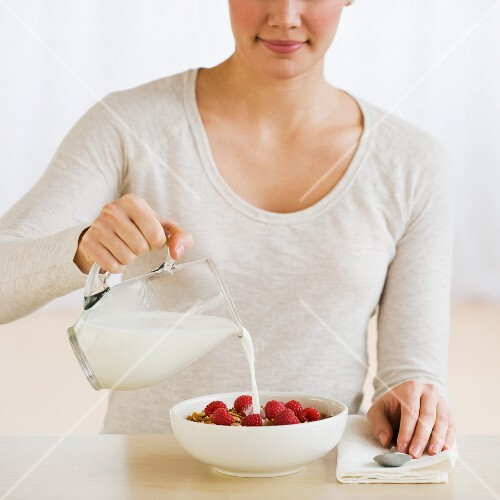 Woman pouring milk on cereal