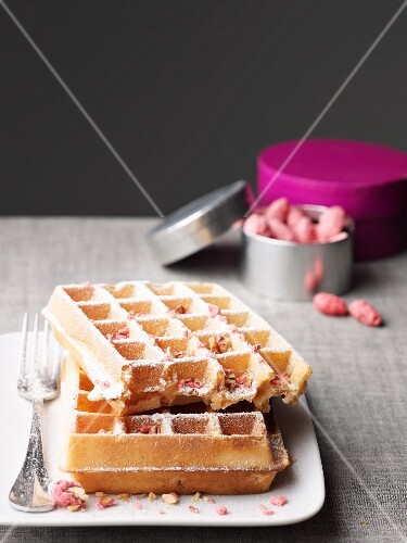 Waffles with pink pralines and icing sugar