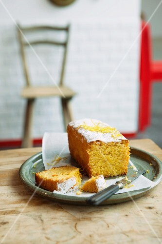 Lemon cake dusted with icing sugar, with a slice cut