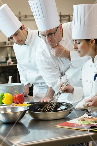 Head chef inspecting cooking techniques
