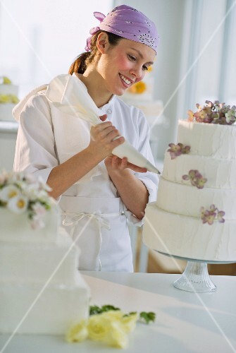 Happy young woman decorating wedding cake