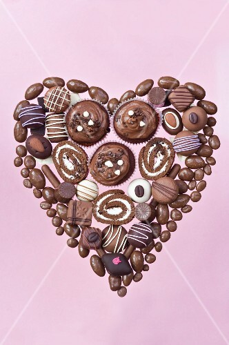 Heart made of chocolate candies, pastries and rolls