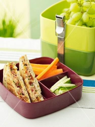 Sandwiches with tuna fish, tomatoes and chorizo, vegetables and grapes in a lunch box