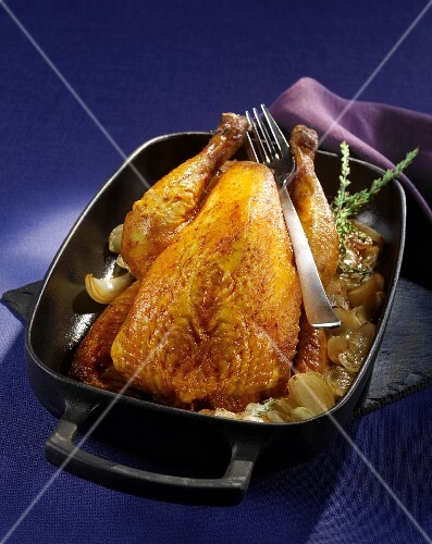 Roasted guinea fowl with onions in the roasting tin