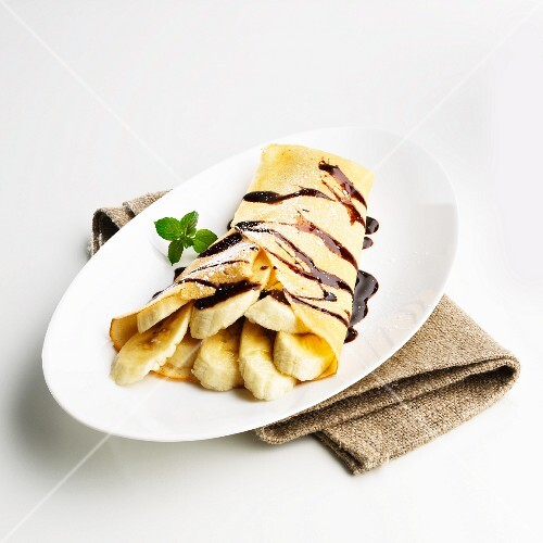 Crepe with banana slices and chocolate sacue