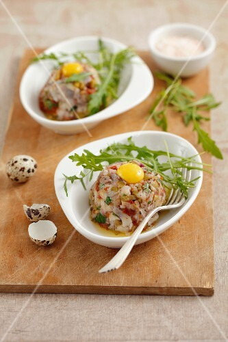 Herring tartare with dried tomatoes, pickled cucumbers and quail egg