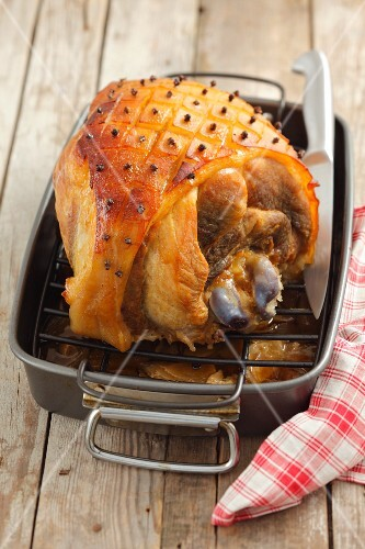 Roasted ham with bone in a roasting dish