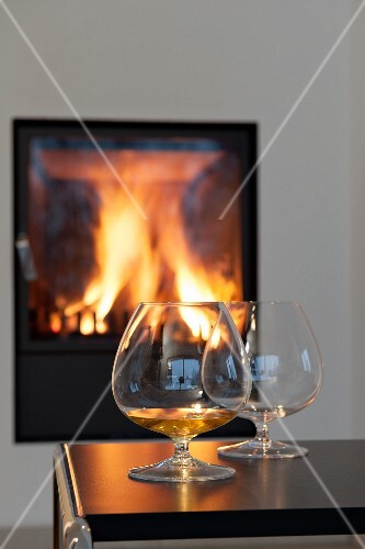 Two cognac snifters on a table in front of a roaring fire in a fireplace