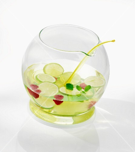 Punch bowl with sliced limes and raspberries