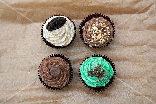 Four cupcakes on rustic paper