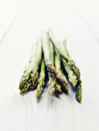 Green asparagus on a white wooden surface