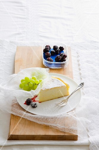 A slice of cheesecake with blackberries and grapes