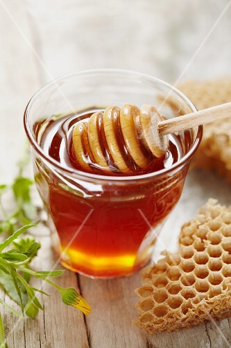 Honey and honey dipper in glass