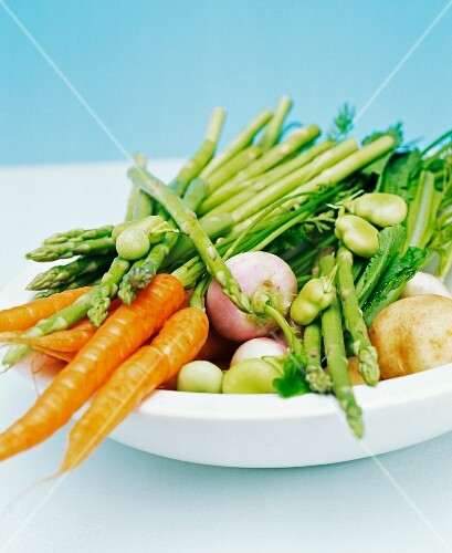 Close up of a bowl filled with spring vegetables including carrots, beans, asparagus, turnip and potatoes