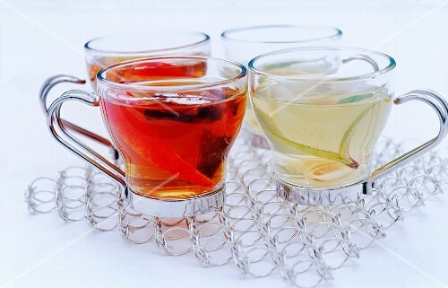 glass cups of black and white tea on a cooling rack