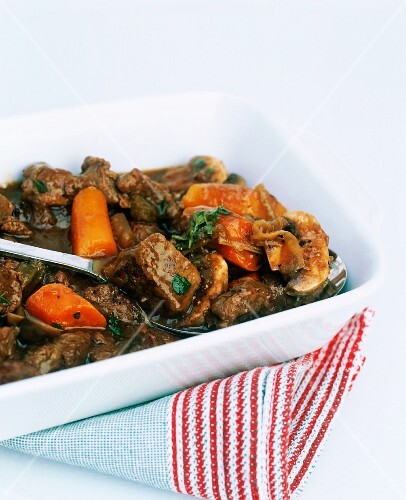 beef casserole with carrots in a white dish with stripy tea towel white cut out