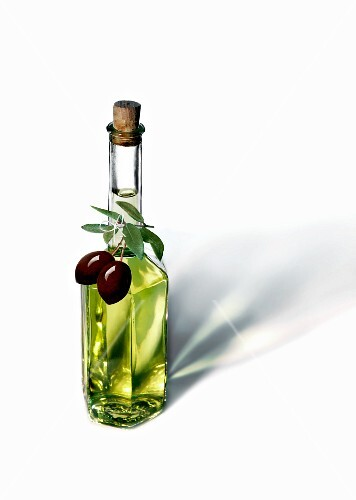 An olive oil bottle with black olives