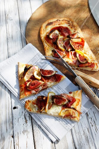 A long thin pizza topped with ham and figs