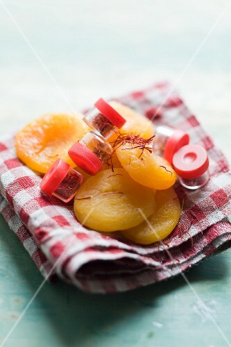 Dried apricots and saffron threads on a checked cloth