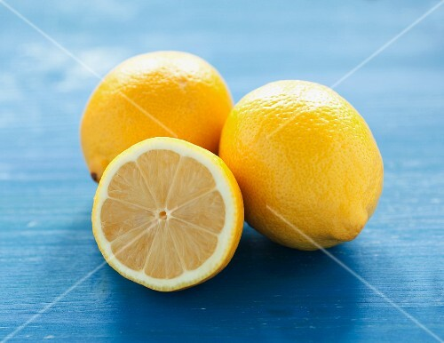 Whole and half lemons on a blue surface
