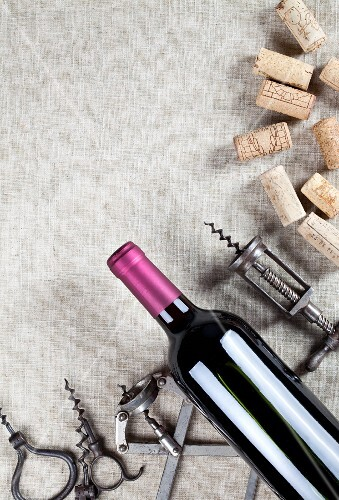 A bottle of red wine, old corkscrews and wine corks
