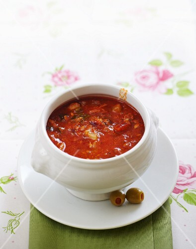 bowl of meat and tomato goulash soup with olives