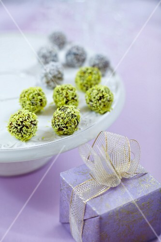 Chocolate truffles with coconut shawings on white plate and gift box