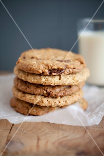 Chocolate chip, peanut butter and oatmeal cookies stacked on baking parchment wih a glass of milk in the background.