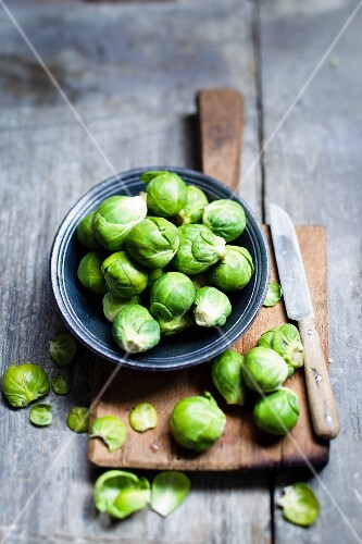 Brussels sprouts in a bowl on a chopping board