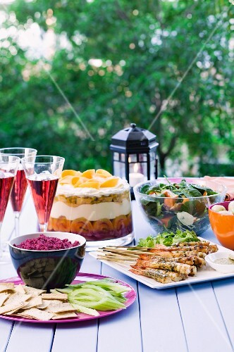 A table in the garden, laid with prawn skewers, beetroot dip, spinach salad and a trifle