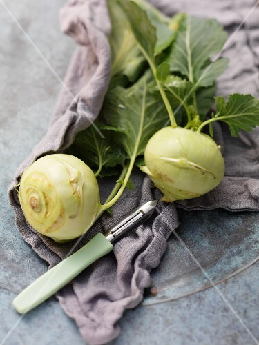 Two kohlrabi with a vegetable peeler