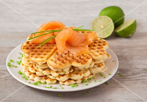 Waffles with salmon, limes and chives on a wooden surface
