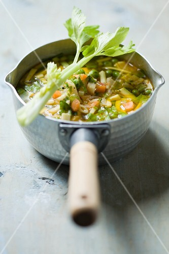 Minestrone soup with celery in a saucepan