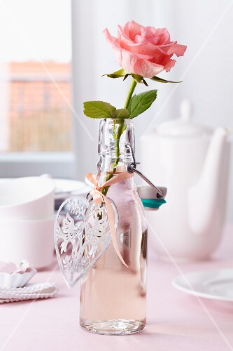 Rose in bottle used as vase with heart-shaped pendant