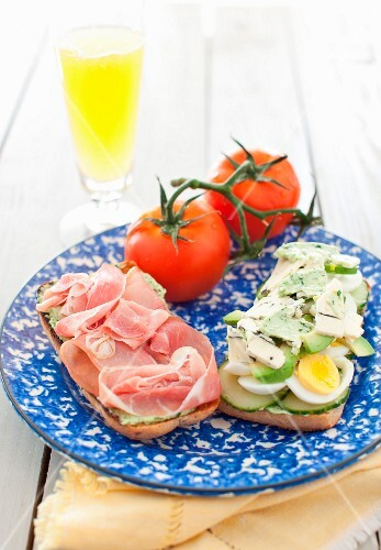An Open Ham, Egg, Cucumber and Avocado Sandwich on a Blue and White Plate; Tomatoes